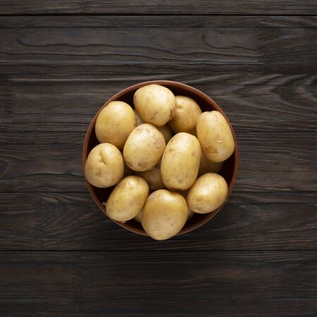 Young unpeeled potatoes in a bowl on a wooden dark table.