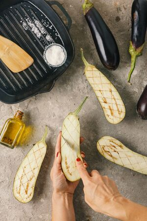 Woman prepares eggplants with vegan stuffing and pine nuts Stock Photo