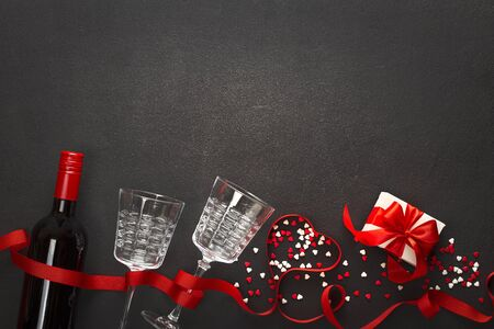 Valentines day background. Wine, hearts, gift, glasses on dark concrete