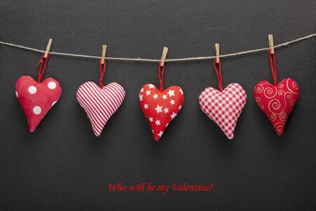 February 14 is Valentines Day. Symbolism of the day of lovers hearts. Homemade hearts on a rope on a dark background 스톡 콘텐츠