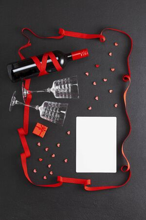 Valentines day background. Wine and two glasses, a gift and a blank sheet for a wish, a gift and red hearts on a black background.