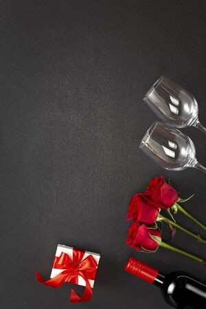Background Womens Day or Valentines Day. Wine, red roses, gift box.