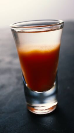 Vodka with tomato juice on a dark background