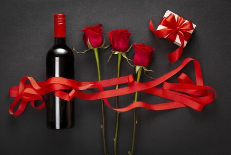 Wine, roses and gift box with a red bow. Love concept.