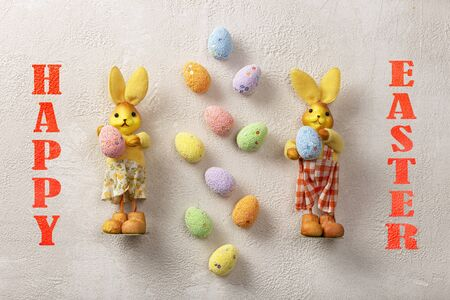 Easter. Easter bunnies and eggs on a light concrete background.