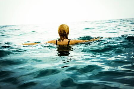girl is on the sea surface. Escape from reality, antistress, relaxation, meditation. Girl in search of relaxation in the sea.