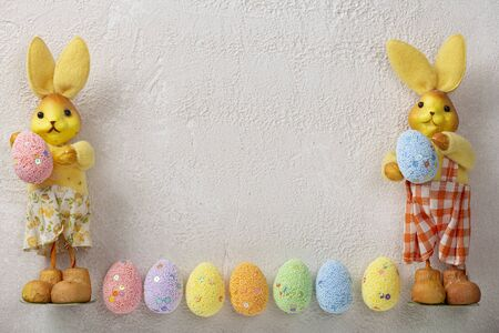 Easter background with easter bunnies and easter eggs. Copy space, light concrete.