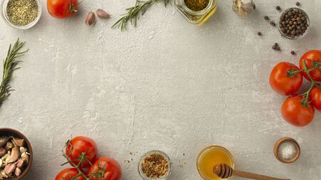 Frame of products on gray concrete. Tomatoes, rosemary, spices, seasonings Copy space