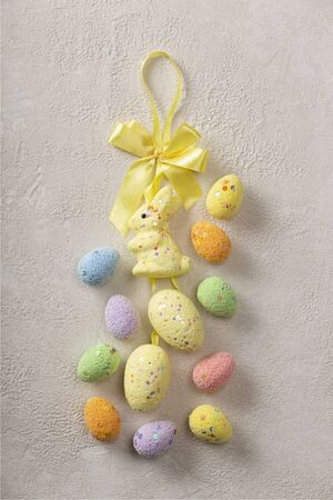 Easter background. Easter bunny and easter eggs on light concrete with copy space.