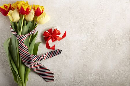 Fathers Day. Holiday background Fathers Day. Mens tie tied to a bouquet of flowers and a gift.
