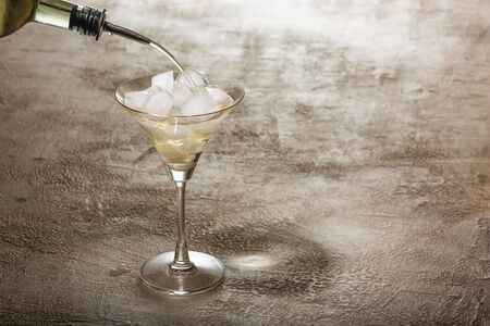 Alcohol is poured into a cocktail glass with ice. Bar concept