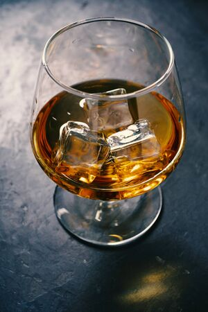 Whiskey, Brandy, cognac, in a glass with ice
