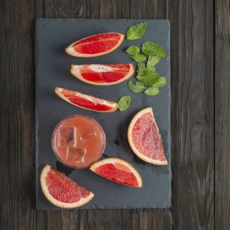 Grapefruit Cocktail. grapefruit arean sliced on a stone board