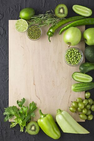 Green vegetables and fruits are a source of vitamins in the diet of vegetarians. Copy space, flat lay. Frame of green products with copy space. Banco de Imagens