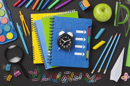 Concept back to school on schedule. alarm clock, notebooks, pencils, student or student tools on the background blackboard for chalk.