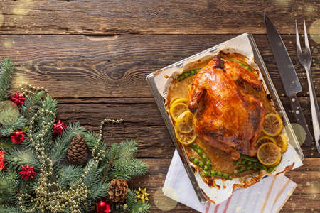 Christmas Dinner. Roasted chicken. Roast turkey over wooden background with christmas tree, table setting with copy space
