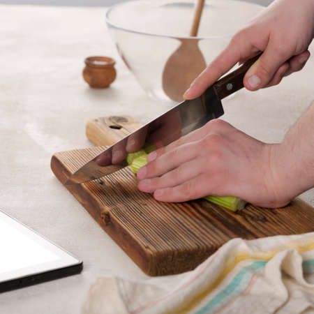 Young chef cook cuts vegetables on a cutting board. Archivio Fotografico