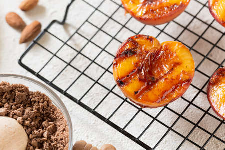 Grilled peaches summer dessert American bbq. Served with almonds, ice cream and cookie crumbs.