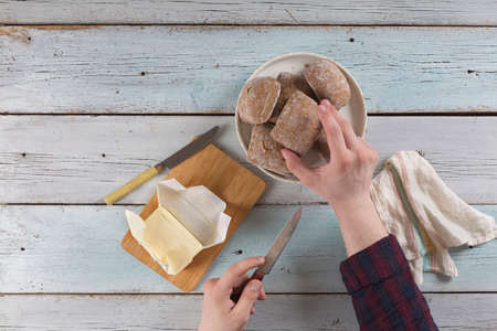 Young man buttering butter on a bun on an old rustic table. Archivio Fotografico