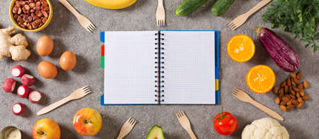 Concept of diet and healthy eating. Notepad with a schedule of food and healthy food, vegetables, fruits, greens, nuts, eggs, legumes. top view