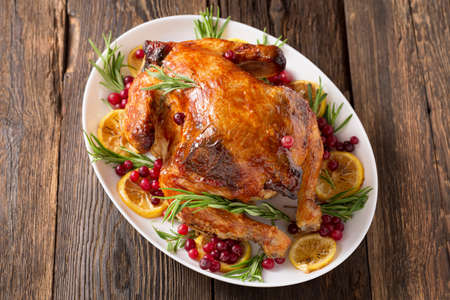 Thanksgiving Day traditional dish baked turkey. Roasted turkey or chicken with orange slices in plate for Christmas dinner on dark rustic background, top view, close up