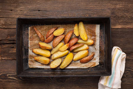 Rustic baked potatoes in a tin form on the dining table. top view