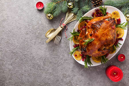 Christmas table with baked chicken is festively decorated with candles. Archivio Fotografico