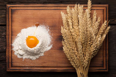 Bread baking bakery concept. Eggs, flour, spikelets on a wooden antique table.