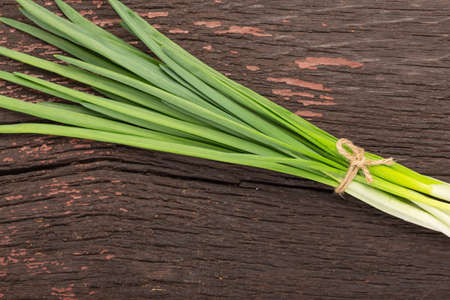 bunch of green onions on a wooden table