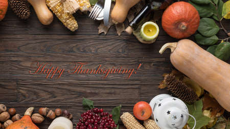 slogan Happy Thanksgiving in a frame of autumn vegetables. Festive table