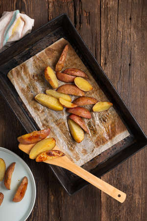 Rustic baked potatoes in a tin form on the dining table. Archivio Fotografico - 155883781
