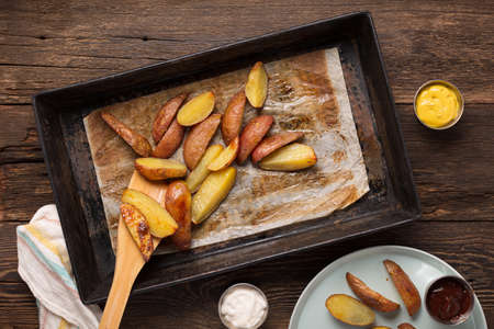 Rustic baked potatoes in a tin form on the dining table. Archivio Fotografico