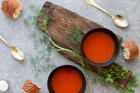 Tomato soup in black bowl on gray stone background. Top view. Copy space. 版權商用圖片