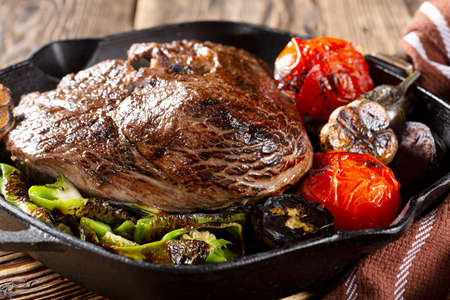 Large piece of meat baked grill close-up. BBQ steak in a pan with vegetables Archivio Fotografico - 156169232
