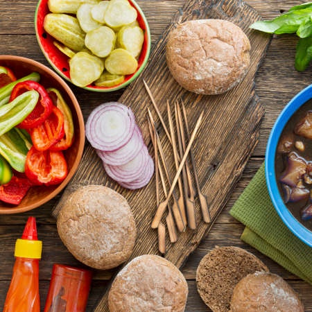 Set of products for cooking burgers. Cooking burgers with vegetables and meat on a wooden table, top view