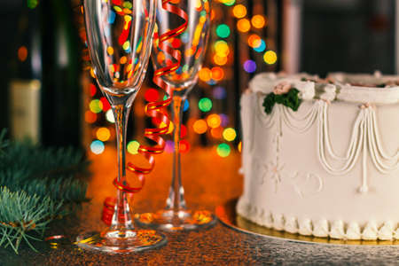 Christmas composition with champagne and multicolored bokeh, close up