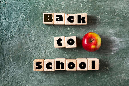 Back to school slogan on wooden cubes. Green blackboard background and ripe apple is a symbol of knowledge., top view