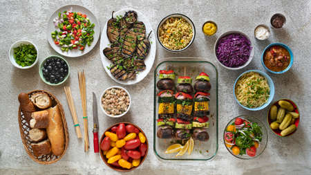 Various vegetarian dishes and salads on a light dining table, top view Archivio Fotografico - 156785800