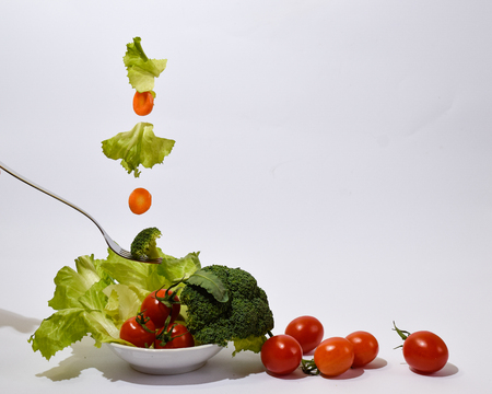 colorful salad of tomato, lettuce, carot and broccoli floating in the air solated on a white background, light meal Imagens