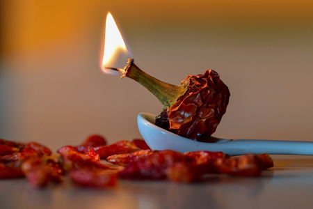 red hot chili pepper burning on spoon Stock Photo