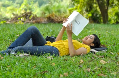 Pretty college girl lays on grass while reading a book Stock Photo