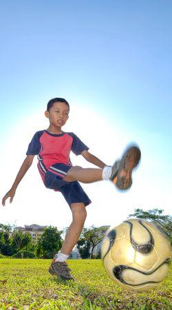 A boy is kicking a ball during evening