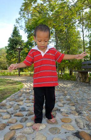 A boy walks on reflexology stones photo