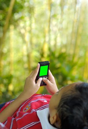 A boy concentrate plays games on mobile phone with green screen