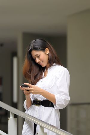 A pretty girl takes a rest while sending message through hand phone Stock Photo