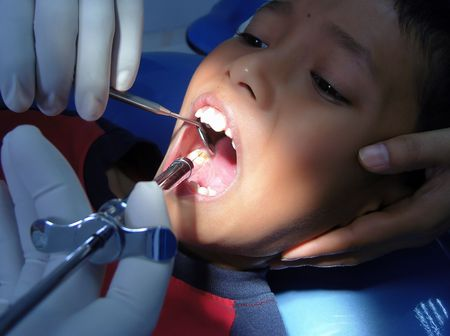 A boy expressions when the needle in his mouth photo