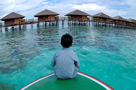 mabul: A boy takes a look at the resort in the middle of Borneo Region of Sabah Mabul Semporna island Stock Photo