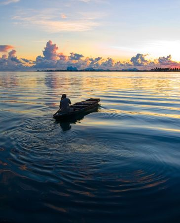 A local fisherman rows his boat during sunrise in the exotic tropical ocean