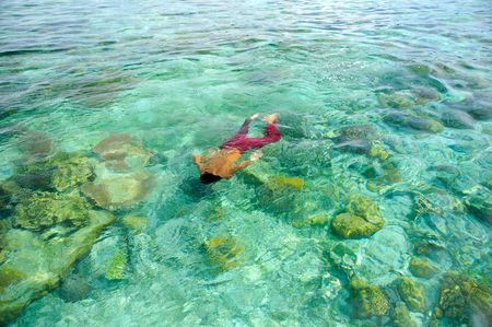A boy swims on clear crystal ocean fills with coral during vacation photo
