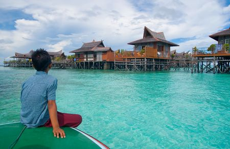 A boy looks at exotic tropical resort in the middle of ocean on crystal clear water